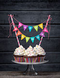 Happy Birthday Cupcakes. Three chocolate cupcakes with vanilla buttercream icing, sprinkles, and a colorful Happy Birthday banner Stock Photo
