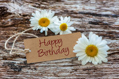 Happy Birthday. Daisy flowers with a tag Happy Birthday on wooden background Stock Photography
