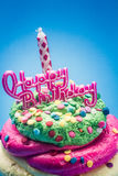 Happy Birthday. Delicious multi-layered cupcake with happy birthday message and candle Royalty Free Stock Photos