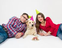 Happy birthday dog with people on white. Happy couple and their dog celebrate one year birthday in studio stock image