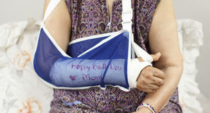 Happy birthday elderly woman with a broken arm. Stock Photo