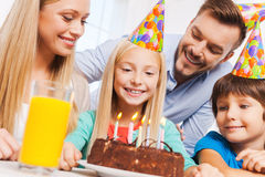 Happy birthday!. Happy family of four celebrating birthday of happy little girl sitting at the table with birthday cake on it stock image