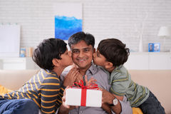 Happy birthday, father. Sons kissing their father in both cheeks Royalty Free Stock Photos