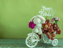 Happy birthday frame. Rabbit on a bicycle with a bouquet of flowers and grapes wishes you a happy birthday Royalty Free Stock Photo