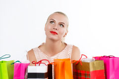 Happy birthday and gifts concept. Beautiful thoughtful blond woman dreaming with colored paper bags with fresh buyings and presents. Shopping, consumerism and Royalty Free Stock Photography