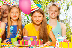 Happy birthday girl in party hat among her friends Stock Photos
