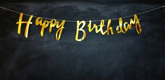 Happy birthday golden garland at a dark wall. Happy birthday garland at a dark wall. The letters are golden royalty free stock images