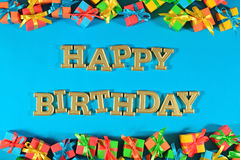 Happy birthday golden text and colorful gifts on a blue royalty free stock photography