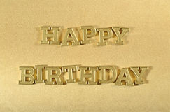 Happy birthday golden text on a golden stock image
