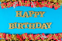 Happy birthday golden text and golden and red gifts on a blue Stock Photography