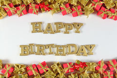 Happy birthday golden text and golden and red gifts on a white stock photos