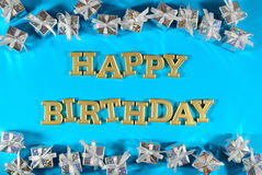Happy birthday golden text and silver gifts on a blue Royalty Free Stock Photo