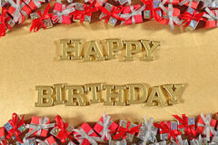 Happy birthday golden text and silver and red gifts stock image