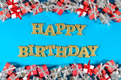 Happy birthday golden text and silver and red gifts on a blue royalty free stock image