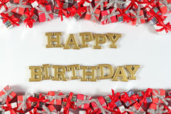 Happy birthday golden text and silver and red gifts on a white royalty free stock image
