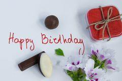 Happy birthday greeting card with gift box, fresh flowers and chocolates. On white background stock images