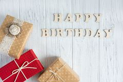Happy Birthday. Greeting inscription from wooden letters on a light wooden background with a gift. Greeting card with a