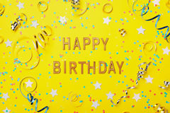 Happy birthday greeting text decorated with confetti and serpentine on yellow background top view. Flat lay style.