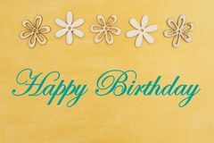 Happy Birthday greeting with wood flowers. On hand painted distressed gold canvas royalty free stock photos