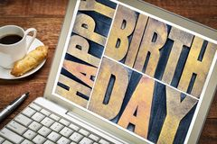 Happy birthday greetings card. In vintage letterpress wood type printing blocks on a laptop screen with a cup of coffee royalty free stock photos