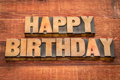 Happy Birthday greetings in wood type. Happy Birthday greetings in letterpress wood type against rustic, red painted barn wood stock images