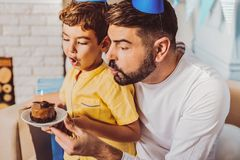 Amazed nice boy celebrating birthday with father. Happy birthday. Happy positive boy and men looking at cake while opening mouth stock image