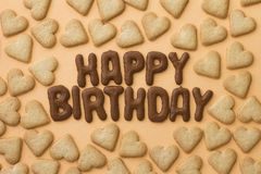 Happy birthday and heart biscuits. Happy Birthday written with Russian bread letter biscuits surrounded by heart-shaped cookies Royalty Free Stock Photography