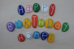 Happy Birthday Honey with colored stones over white sand