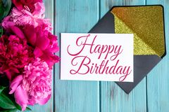 Happy birthday lettering with peony flowers and a card on a blue wooden background. Greeting card for the birthday of mom,