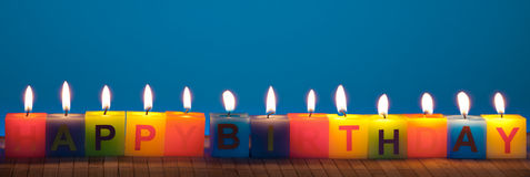 Happy birthday lit candles on blue Stock Photo