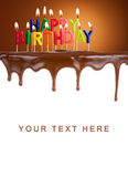 Happy birthday lit candles on chocolate cake