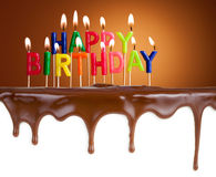 Happy birthday lit candles on chocolate cake Royalty Free Stock Photography