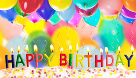 Happy birthday lit candles on colorful balloons. Background Royalty Free Stock Image