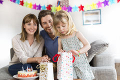 Happy birthday little girl. Gift for you. Cheerful parents celebrating daughter's birthday offering a present stock images