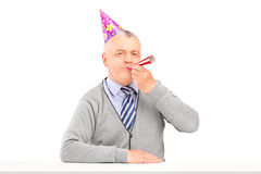 Happy birthday mature man with party hat blowing. Isolated against white background stock images