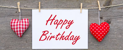Happy birthday message. In red text on white card pegged to a washing line along with decorated hearts on either side all on a background of gray wood Royalty Free Stock Image