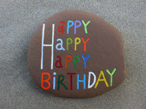 Happy birthday message. Colorful text 'Happy birthday' with happy repeated three times inscribed on a brown stone lying on gray textured sand Stock Photos
