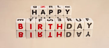 Happy birthday message. Text ' happy birthday ' inscribed in uppercase letters on small cubes placed in two rows  on bright background Royalty Free Stock Images