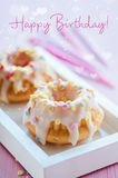 Happy Birthday!. Mini birthday cake on pink wooden background with cute heart bokeh Royalty Free Stock Images
