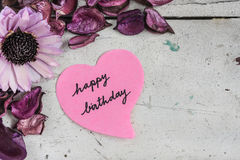 Happy birthday note in heart shape paper with pink flowers royalty free stock photo