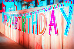 Happy Birthday Paper Inscription. Motley Happy Birthday banner hanging on a wooden background. Selective focus Stock Photos