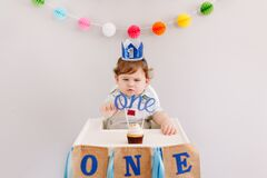 Happy birthday party. Cute Caucasian baby boy in blue crown celebrating first birthday at home. Child toddler in a high chair