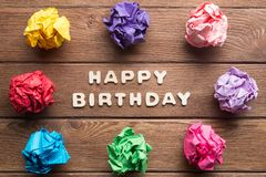 Happy birthday phrase and colorful crampled paper ball placed in circle on wooden table. Set of multiple colorful crampled paper ball placed in circle on wooden stock photo