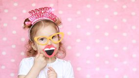 Happy birthday. Portrait sweet little girl with glasses, who smiling, have fun, laugh and celebrate. Congratulation. Close-up funny child on pink background stock footage
