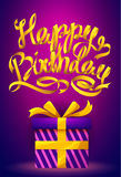 Happy Birthday poster - gold ribbon lettering and gift box on purple background. Stock Photography