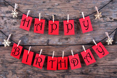 Happy Birthday on Red Tags. Red Tags Hanging on a Line with the Words Happy Birthday on it, Wooden Background Royalty Free Stock Photos