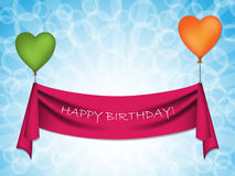 Happy birthday ribbon on heart balloons. Happy birthday ribbon hanging on heart shaped balloons Royalty Free Stock Photography