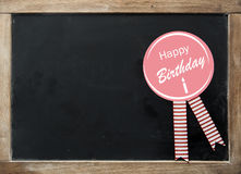Happy Birthday rosette on a vintage slate Royalty Free Stock Photography