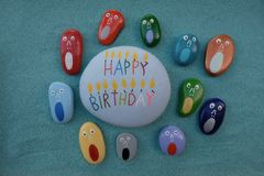 Happy Birthday with the screamers. Stones design composition over green sand for a unique happy birthday invitation card Royalty Free Stock Images