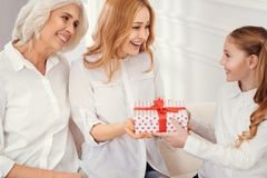 Loveful mom and granny giving gift box to granddaughter. Happy birthday. Selective focus on tender women looking at a little girl with eye full of love while Royalty Free Stock Image